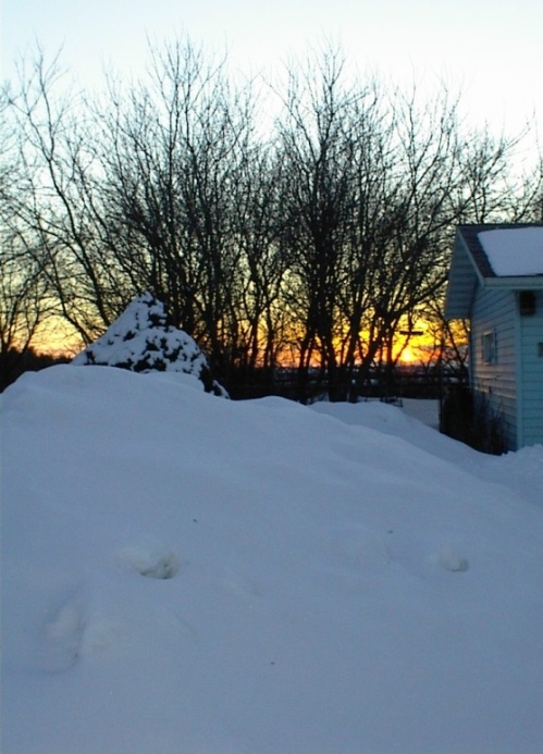 Winter's last sunset with mounds to go before Spring.